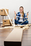 Woman sitting on the floor with screwdrivers. Smiling woman sitting on the floor with screwdrivers and boxes assembling wooden furniture. Girl moving in new royalty free stock photography