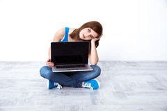 Woman sitting at floor and showing laptop screen Stock Images