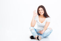 Woman sitting on the floor and showing ok sign Royalty Free Stock Photo