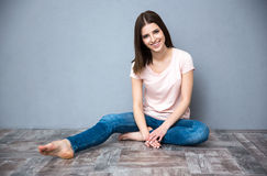 Woman sitting on the floor. Smiling young cute woman sitting on the floor Stock Photo