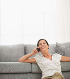 Woman sitting on floor and speaking cell phone Royalty Free Stock Image