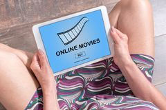 Online movie concept on a tablet. Woman sitting on the floor with a tablet showing online movie concept Stock Image
