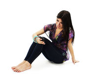 Woman sitting on floor and text messaging on a mobile phone Stock Photography