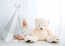 Woman sitting on a floor with a toy teddy. Blonde girl sitting on a floor with a toy teddy in the white room near wigwam stock photography