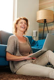 Woman sitting on floor typing on laptop laughing Royalty Free Stock Photography