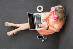 Woman sitting on the floor and using computer Royalty Free Stock Photography