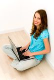 Woman sitting on floor using laptop Royalty Free Stock Photo