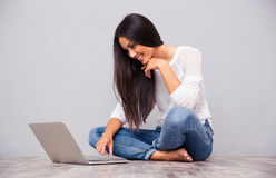 Woman sitting on the floor and using laptop Stock Photo