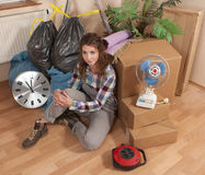 Woman sitting on the floor between waste and moving boxes. In her apartement Royalty Free Stock Photos