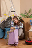 Woman sitting on the floor between waste and moving boxes. In her apartement Stock Image