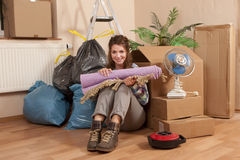 Woman sitting on the floor between waste and moving boxes. In her apartement Stock Photo