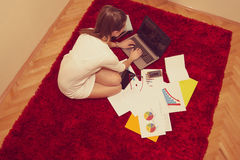 Woman sitting on the floor and working on laptop Royalty Free Stock Photo