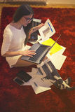 Woman sitting on the floor and working on laptop Stock Photography