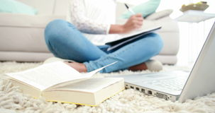 Woman sitting on the floor writing on notepad
