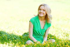 Woman sitting on flower field Stock Photos