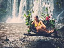 Woman sitting in flowered swing near waterfall, Phnom Koulen at Siem Reap, Cambodia. Beautiful woman sitting in flowered swing near waterfall, Phnom Koulen at Stock Photo