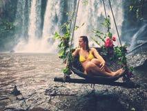 Woman sitting in flowered swing near waterfall, Phnom Koulen at Siem Reap, Cambodia Stock Photo