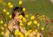 Woman sitting in flowers Stock Photography