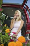 Woman sitting by flowers on back of minivan using cell phone Royalty Free Stock Photography