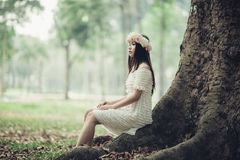 Woman sitting at foot of tree Stock Photography