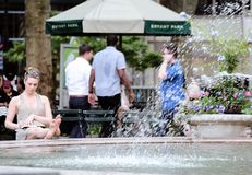 Young Woman Sitting Barefoot by a Fountain, Bryant Park, New York City. A women relaxing barefoot and writing in a notebook sitting by the running water from the royalty free stock images