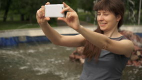 Woman sitting by the fountain with the phone. Young happy woman in gray blouse creates a self-portrait on the phone sitting next to a fountain in the summer day stock video
