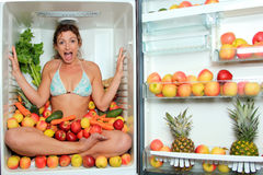 Woman sitting in a fridge. In the lotus position surrounded by fruits royalty free stock image