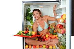 Woman sitting in a fridge. In the lotus position surrounded by fruits holding a cutting board with cut apples stock photo