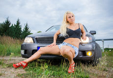 Woman sitting in front of car. Royalty Free Stock Photo