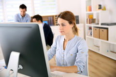 Woman sitting in front of computer in office Royalty Free Stock Images