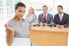 Woman sitting in front of corporate personnel officers. Portrait of women sitting in front of corporate personnel officers in office royalty free stock photos