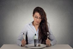 Woman sitting in front of a dish looking at a tiny man. Portrait young woman sitting at table in front of a dish looking at a tiny man on gray wall background stock image