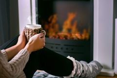 Woman sitting in front of the fireplace and holding cup of tea in hand on legs royalty free stock photos