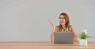 Woman sitting in front of laptop and showing hand on blank wall Stock Photography