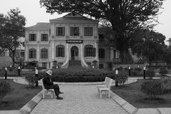 A woman is sitting in front of a library in Hanoi (Vietnam) Royalty Free Stock Image