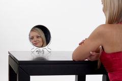 Woman Sitting in front of mirror Stock Images
