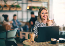 Woman sitting in front of open laptop computer in cafe Stock Photo