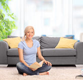 Woman sitting in front of a sofa and holding book Stock Photography