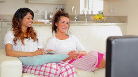 Woman sitting in front of the TV. Women sitting on the couch in front of the TV stock video