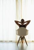 Woman sitting in front of window. Rear view. Woman sitting in front of window in room. Rear view Royalty Free Stock Photos