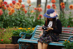 Woman sitting in the garden. Woman looking at photo on dslr camera in the flowers garden park royalty free stock photo
