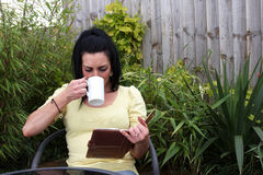 A woman sitting in the garden reading Stock Photos