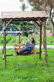 Woman sitting on the garden swing Stock Images