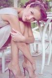 Woman sitting in a gazebo wearing a beige silk dress Royalty Free Stock Images