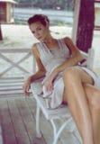 Woman sitting in a gazebo wearing a beige silk dress stock photos
