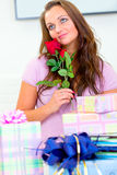 Woman sitting among gifts and holding rose in hand Stock Photography