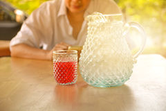 Woman sitting and glass of sweet drink with jar on table. Stock Photography