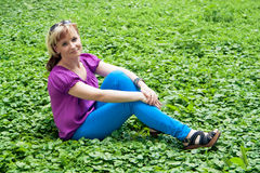 Woman sitting on the grass Stock Images