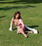 Woman sitting on the grass. Woman sitting on the green grass Royalty Free Stock Images