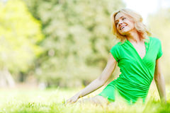 Woman sitting on grass Stock Images